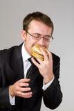 Uomo d'affari affamato che mangia hamburger Immagini Stock Libere da Diritti