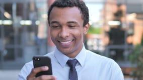 Uomo d'affari africano all'aperto che per mezzo dello smartphone archivi video