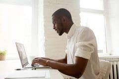 Uomo d'affari africano che lavora al computer portatile che si siede a casa il DES dell'ufficio Fotografia Stock Libera da Diritti