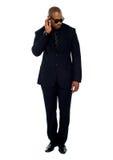 Uomo d'affari africano che prova ad ascoltare qualcosa Fotografia Stock