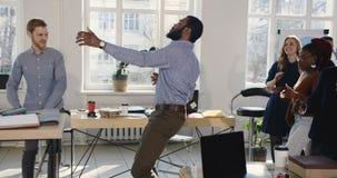 Uomo d'affari africano di divertimento felice che balla insieme ai colleghi multietnici che celebrano le feste nel luogo di lavor stock footage