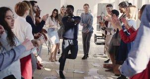 Uomo d'affari africano felice di divertimento giovane che fa ballo sciocco del vincitore che celebra successo con i colleghi al p video d archivio