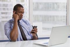 Uomo d'affari afroamericano allo scrittorio facendo uso dello smartphone, orizzontale Immagine Stock Libera da Diritti