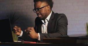 Uomo d'affari afroamericano arrabbiato che lavora tardi al computer portatile in ufficio alla notte Finisce di lavorare archivi video