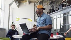 Uomo d'affari afroamericano bello che lavora al computer portatile che si siede sulla tavola mentre i suoi colleghi sono sedentes video d archivio