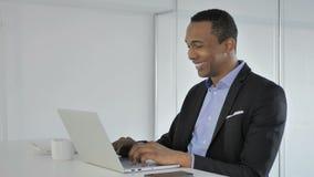 Uomo d'affari afroamericano casuale Celebrating Success, lavorante al computer portatile video d archivio
