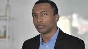 Uomo d'affari afroamericano casuale di pensiero in ufficio, 'brainstorming' video d archivio