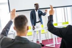 Uomo d'affari afroamericano che dà presentazione che discute progetto con il gruppo multi-etnico all'addestramento corporativo In immagini stock