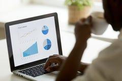 Uomo d'affari afroamericano che lavora con le statistiche di progetto sopra immagini stock