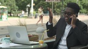 Uomo d'affari afroamericano che negozia dal telefono, difendendo i suoi interessi e parere stock footage
