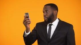 Uomo d'affari afroamericano che riceve buone notizie, strumento finanziario mobile, promozione stock footage