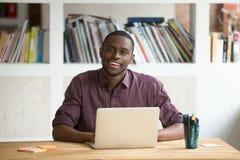 Uomo d'affari afroamericano che si siede allo scrittorio con lo sguardo del computer portatile Fotografia Stock Libera da Diritti
