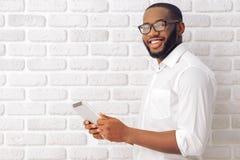 Uomo d'affari afroamericano con l'aggeggio Immagine Stock