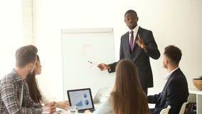 Uomo d'affari afroamericano sicuro che dà presentazione al gruppo multi-etnico con flipchart archivi video