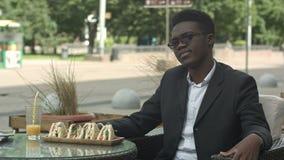 Uomo d'affari afroamericano stanco che si siede in caffè che sembra annoiato o alimentato su video d archivio