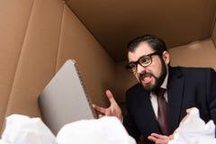 Uomo d'affari aggressivo con il computer portatile del cartone fotografia stock