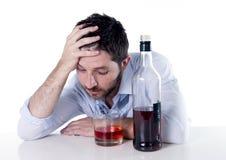 Uomo d'affari alcolico potabile allo scrittorio su fondo bianco Fotografia Stock