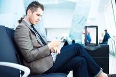 Uomo d'affari all'aeroporto con lo smartphone e la valigia Immagini Stock
