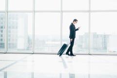 Uomo d'affari all'aeroporto internazionale che si muove verso il portone terminale per il viaggio di viaggio dell'aeroplano che g fotografia stock