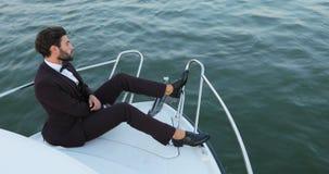 Uomo d'affari alla moda su un yacht o su una barca contro un mare È soddisfatto con il successo nel suo affare e nel suo gruppo video d archivio