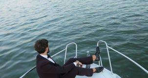 Uomo d'affari alla moda su un yacht o su una barca contro un mare È soddisfatto con il successo nel suo affare e nel suo gruppo archivi video