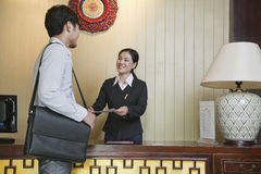 Uomo d'affari alla reception dell'hotel, receptionist sorridente Immagine Stock