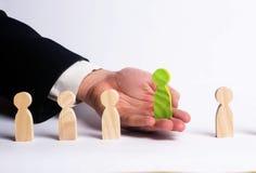 Uomo d'affari alla ricerca di nuovi impiegati Figura verde Il concetto della selezione e della gestione di personale all'interno  fotografie stock