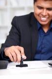 Uomo d'affari alla sua timbratura dello scrittorio Immagini Stock Libere da Diritti