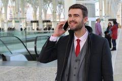 Uomo d'affari allegro che chiama dal telefono dalla stazione ferroviaria immagine stock