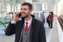 Uomo d'affari allegro che chiama dal telefono dalla stazione ferroviaria fotografia stock
