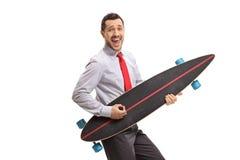 Uomo d'affari allegro che finge di giocare chitarra su un longboard immagini stock