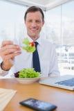 Uomo d'affari allegro che mangia un'insalata Fotografia Stock Libera da Diritti