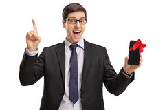 Uomo d'affari allegro che mostra un telefono e che indica su Immagini Stock Libere da Diritti