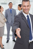Uomo d'affari allegro che si presenta che dà la sua mano Fotografie Stock Libere da Diritti