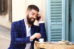Uomo d'affari allegro che si siede al caffè con caffè che parla sul cellulare Fotografie Stock