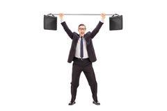 Uomo d'affari allegro che solleva due cartelle su una barra Fotografia Stock Libera da Diritti