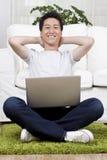 Uomo d'affari allegro facendo uso di un computer portatile su tappeto Fotografie Stock Libere da Diritti