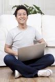 Uomo d'affari allegro facendo uso di un computer portatile sul pavimento Fotografia Stock Libera da Diritti