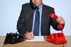 Uomo d'affari allo scrittorio che risponde a due telefoni. Fotografie Stock Libere da Diritti