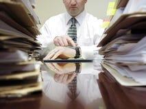 Uomo d'affari allo scrittorio con gli archivi che indica all'orologio fotografia stock