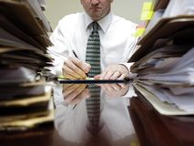Uomo d'affari allo scrittorio con i mucchi degli archivi fotografie stock