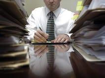 Uomo d'affari allo scrittorio con i mucchi degli archivi e delle carte fotografia stock