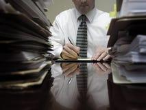 Uomo d'affari allo scrittorio con i mucchi degli archivi e delle carte fotografie stock libere da diritti