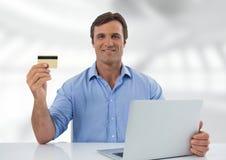 Uomo d'affari allo scrittorio con il computer portatile con fondo e la carta assegni luminosi Fotografia Stock