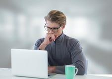 Uomo d'affari allo scrittorio con il computer portatile con fondo luminoso Fotografie Stock