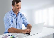 Uomo d'affari allo scrittorio con il computer portatile con fondo luminoso Fotografia Stock