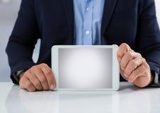 Uomo d'affari allo scrittorio con la compressa con fondo luminoso Fotografia Stock