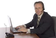 Uomo d'affari allo scrittorio con la cuffia avricolare Fotografia Stock