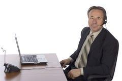 Uomo d'affari allo scrittorio con la cuffia avricolare Immagini Stock