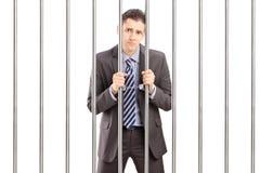 Uomo d'affari ammanettato triste in vestito che posa nella prigione e che tiene le sedere Fotografie Stock